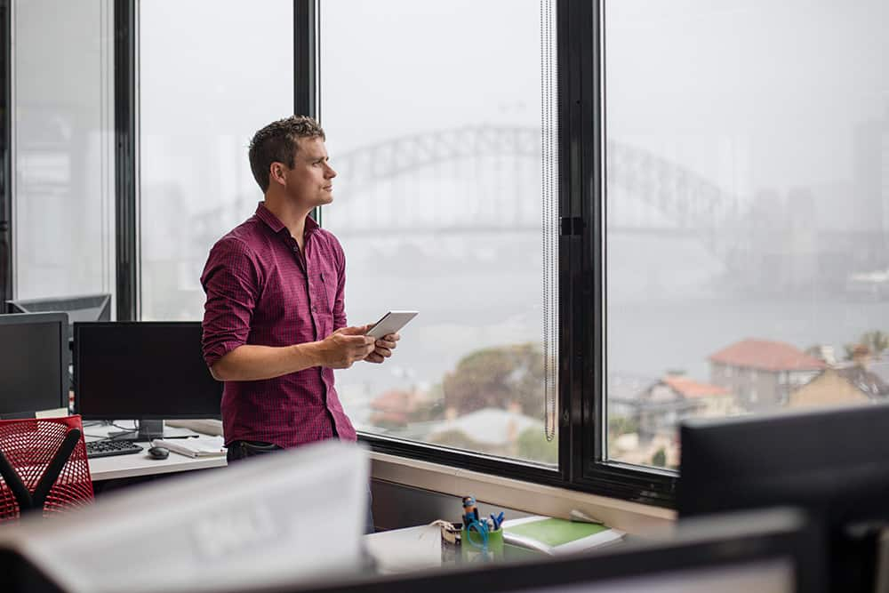 A professional gazing out of an office window