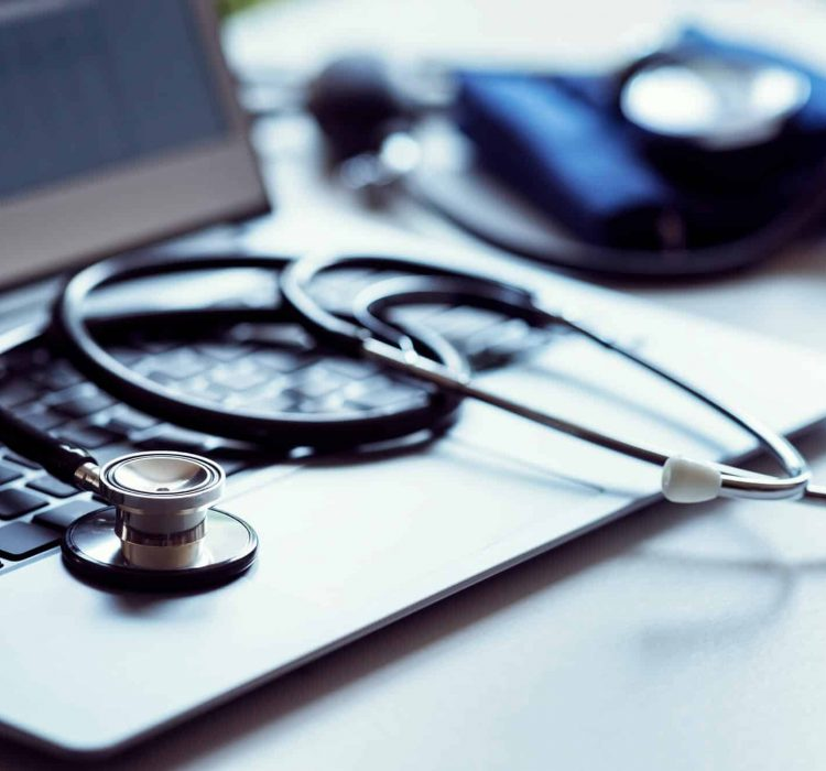 stethoscope-on-laptop-keyboard-in-doctor-surgery-cropped